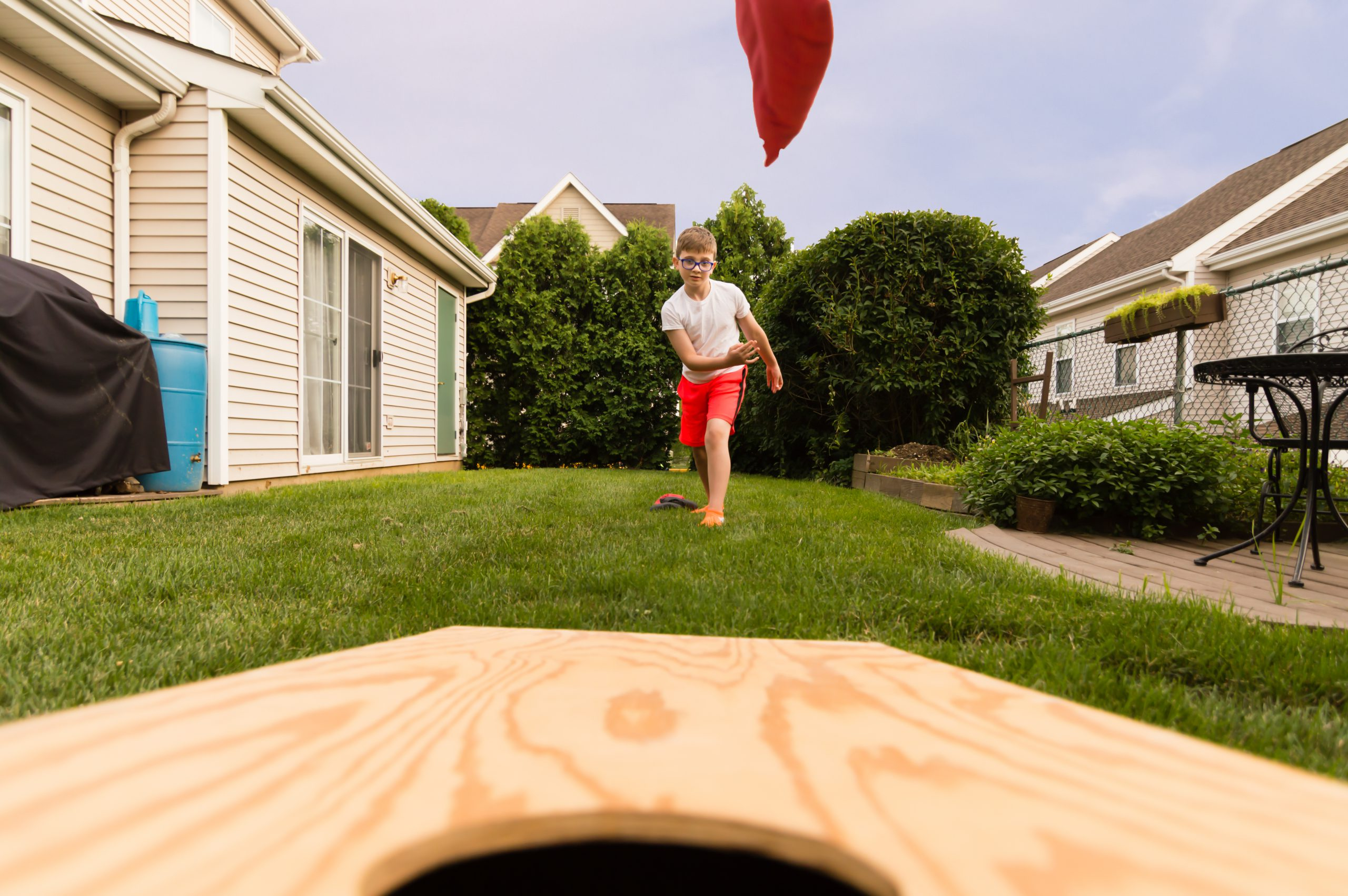 little boy plays a game of cornhole