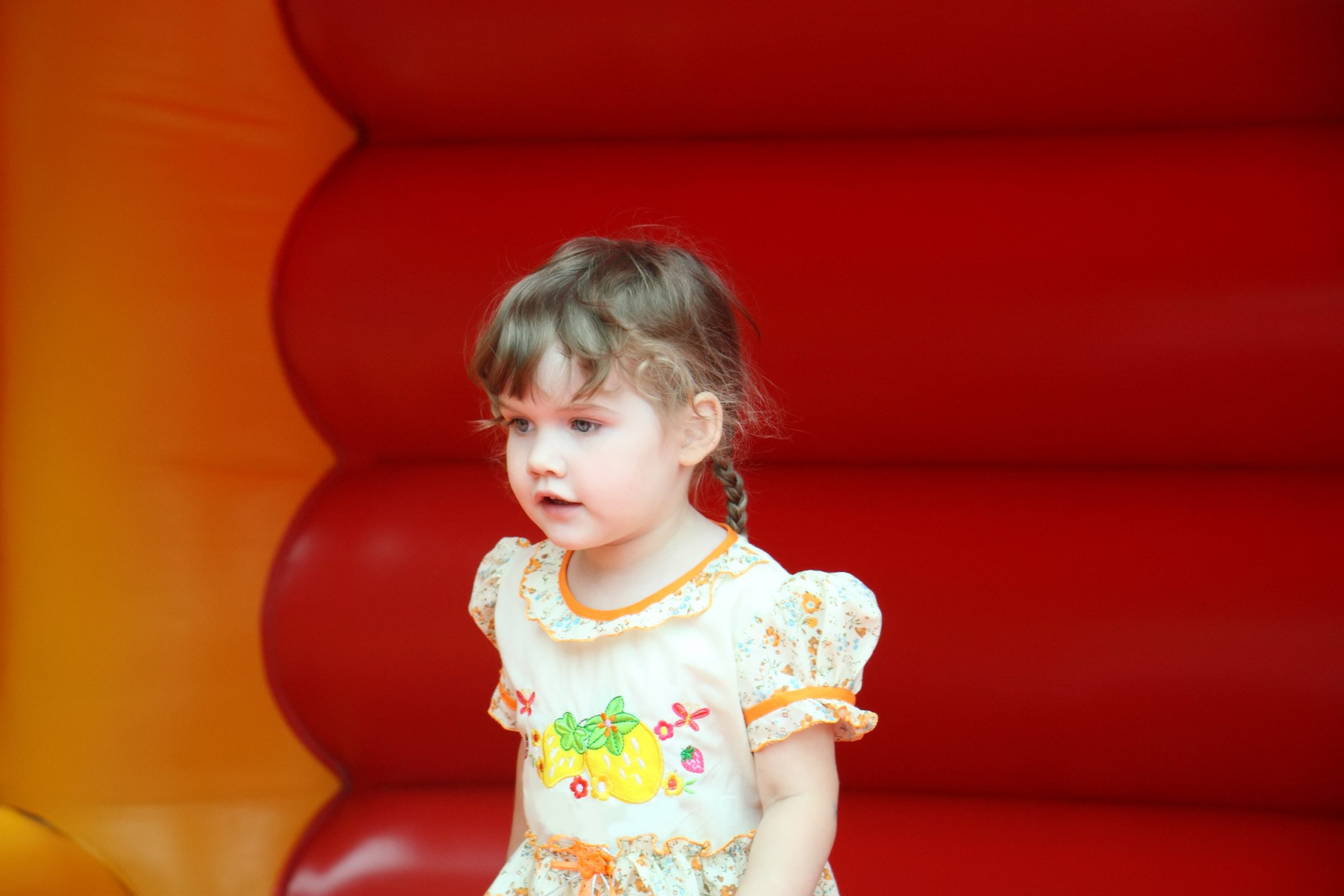 Little beautiful happy girl jumps on red bouncy castle and looks